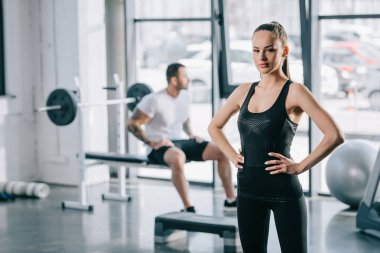 young sportswoman with hands on thighs and man sitting behind at gym