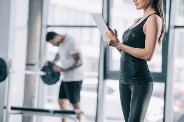 cropped image of female personal trainer with digital tablet and athletic man with barbell at gym