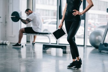 cropped shot of female personal trainer with digital tablet and athletic man exercising with barbell at gym