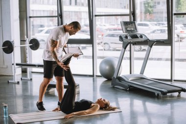 male personal trainer helping young athletic woman to do abs on fitness mat at gym