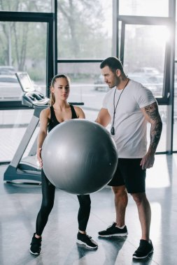 male personal trainer looking at athletic woman exercising with fitness ball at gym