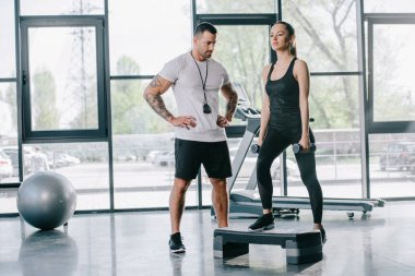 male personal trainer and young sportswoman doing step aerobics exercise with dumbbells at gym