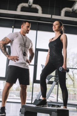 low angle view of male personal trainer and young sportswoman doing step aerobics exercise with dumbbells at gym