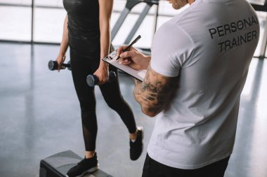 cropped image of male personal trainer writing in clipboard and young sportswoman doing step aerobics exercise with dumbbells at gym