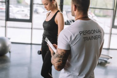 rear view of male personal trainer with clipboard and young sportswoman with dumbbells at gym