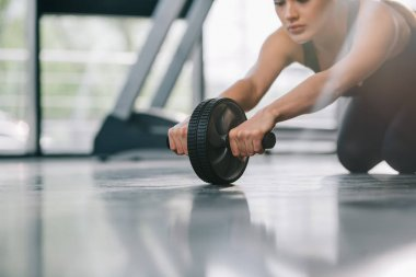 cropped image of young sportswoman doing exercise with abs roller at gym