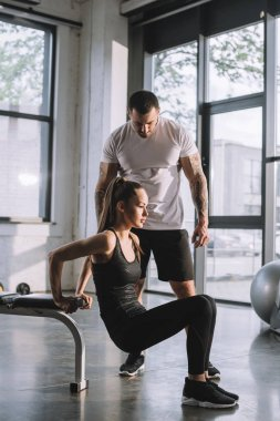 male personal trainer looking at sportswoman doing plank at gym