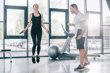 male personal trainer using timer while sportswoman exercising with jump rope at gym