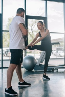 male personal trainer helping sportswoman to stretching at gym