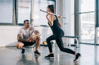 male personal trainer looking at sportswoman doing sit ups with barbell bar at gym