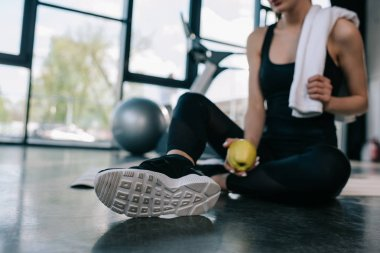cropped shot of sportswoman resting with towel and apple on gym floor