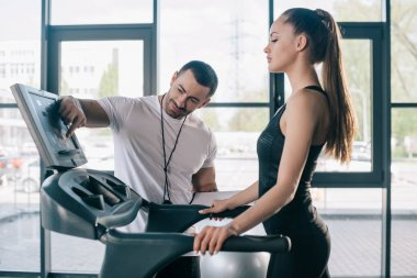 male personal trainer pointing at treadmill screen and sportswoman standing near at gym