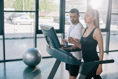 male personal trainer looking at treadmill screen while sportswoman running at gym