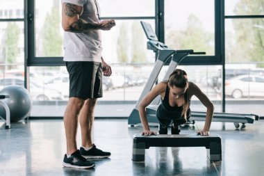 male personal trainer using timer while sportswoman doing push ups at gym