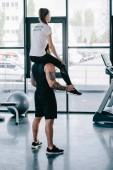 Fotografie Sportler dabei Sit Ups mit weiblichen personal Trainer sitzen auf seinen Schultern im Fitnessstudio