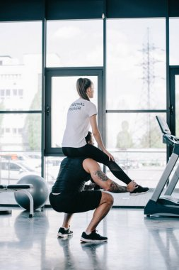 sportsman doing sit ups with female personal trainer sitting on his shoulders at gym