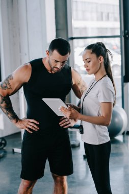 female personal trainer and sportsman looking at screen of digital tablet at gym