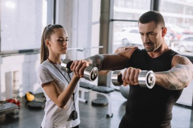 female personal trainer helping sportsman to do exercises with dumbbells at gym