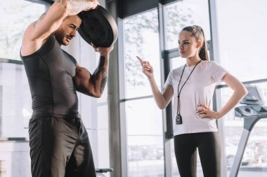 female personal trainer counting while sportsman doing exercises with barbell disc at gym