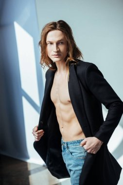 shirtless man in black jacket, on grey