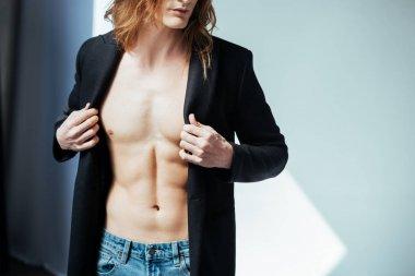 cropped view of shirtless man in black jacket, on grey