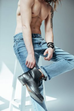 cropped view of sexy shirtless man posing in jeans, on grey