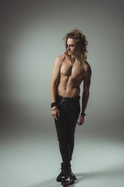 shirtless man with long hair posing in black jeans, on grey