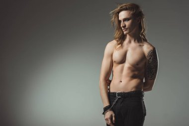 handsome shirtless man with tattoo posing in black jeans, isolated on grey