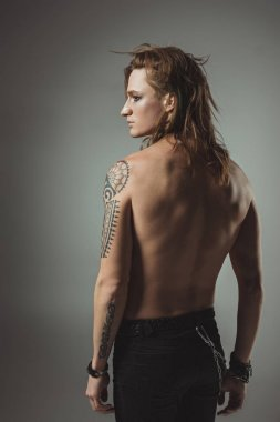 shirtless tattooed man with long hair posing in black jeans, isolated on grey