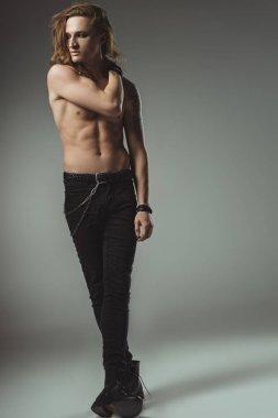 shirtless stylish man posing in black jeans, on grey