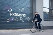 Photo smiling young businessman in suit riding bicycle on street with progress inscription and business icons on gate entrance
