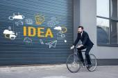 Fotografie usmíval se mladý podnikatel v obleku, jízda na kole na ulici s myšlenkou nápis a obchodní ikony na vstupní bráně