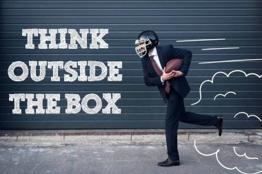 side view of businessman in suit and rugby helmet with ball in hands running on street with think outside box inscription
