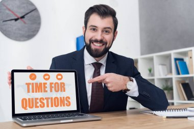 portrait of cheerful businessman pointing at laptop with time for questions inscription at workplace in office