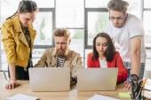 Rozmanité obchodní tým pracující na projektu a při pohledu na notebook obrazovkách v lehké prostoru