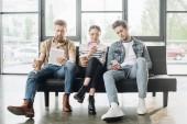 Profesionální obchodní kolegové muži a žena při pohledu do obrazovky digitálních zařízení v moderní kanceláři