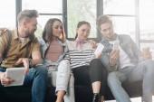 Rozmanité obchodní tým při pohledu na obrazovku smartphonu v lehké prostoru