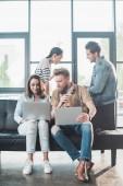 Úspěšní podnikatelé, pracující na notebooky a diskusi o projektu v moderní lehké úřadu