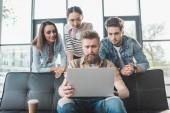 Fotografie Geschäftsleute betrachten ihren männlichen Kollegen, der im modernen Lichtbüro am Laptop arbeitet