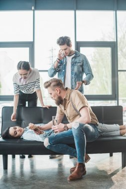 Businessman checking pulse of young fainted woman lying on sofa in office