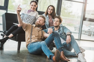 Diverse business team taking selfie in light workspace stock vector