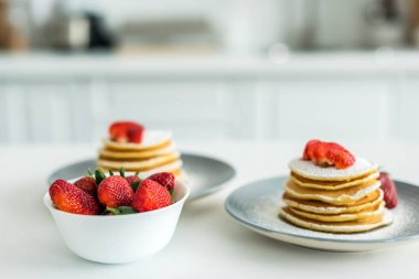 pancakes with ripe strawberries on table at kitchen