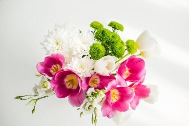 top view of bouquet of beautiful tulips on white table at kitchen