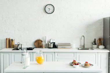 interior of kitchen with yummy pancakes and orange juice on kitchen counter