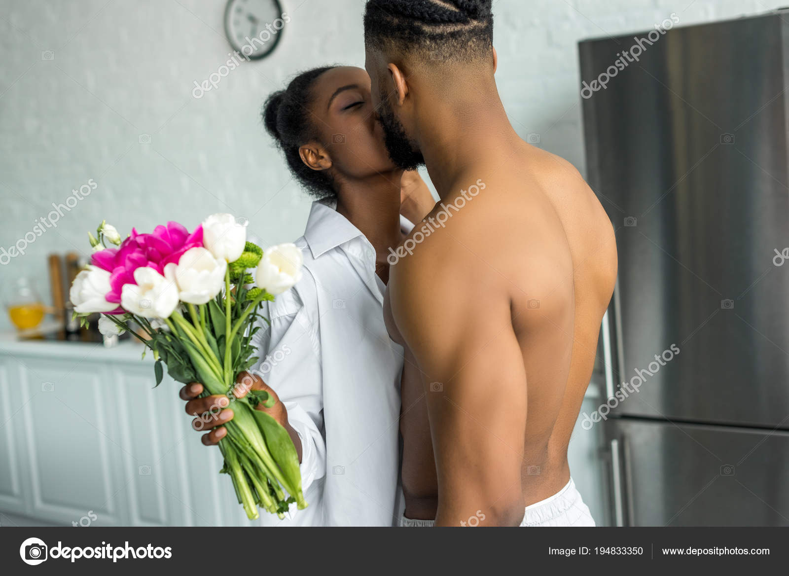 African American Couple Kissing Girlfriend Holding Bouquet Kitchen
