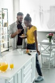 smiling african american boyfriend feeding girlfriend with strawberry at kitchen