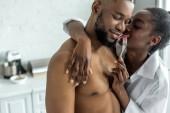 Fotografie Afrikanische amerikanische Freundin Freund umarmt und ihm Stück Erdbeere in Küche