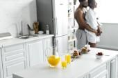 Fotografie americký pár objímat s jídlem na popředí v kuchyni