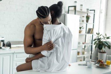 african american boyfriend kissing girlfriend neck at kitchen