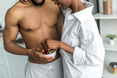 cropped image of african american couple eating strawberries at kitchen